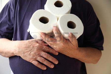 29673165 homme avec la main sur son ventre detient trois rouleaux de papier de toilette